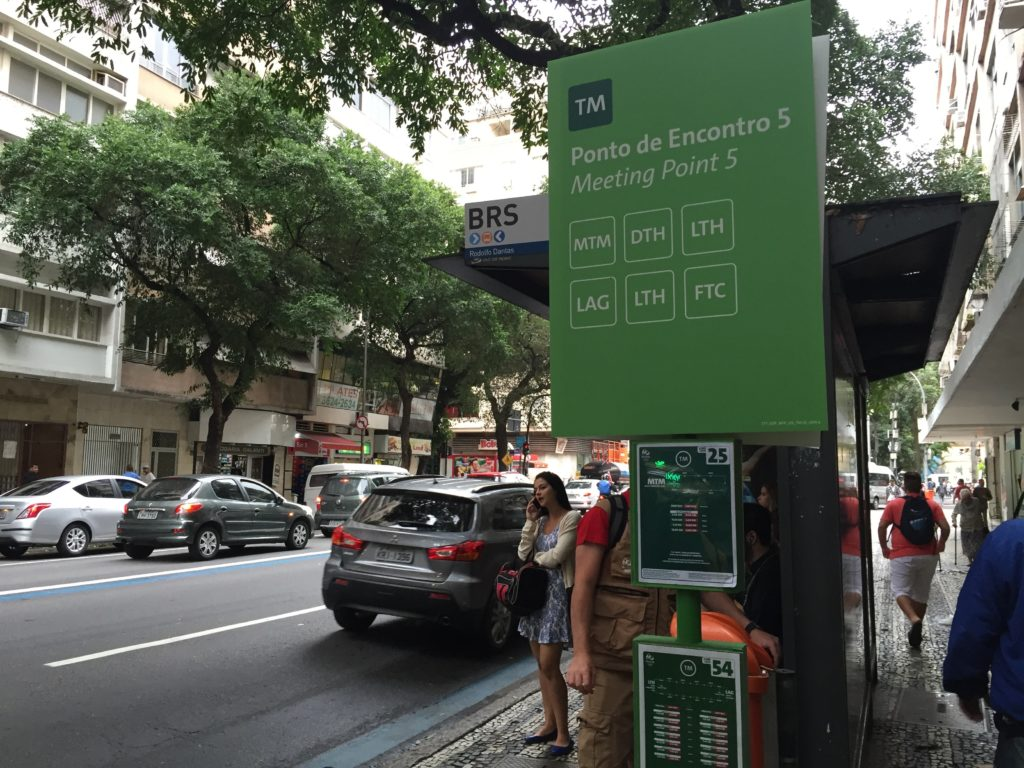 Signage indicating a Rio bus stop is also a stop within the credentialed transportation system.